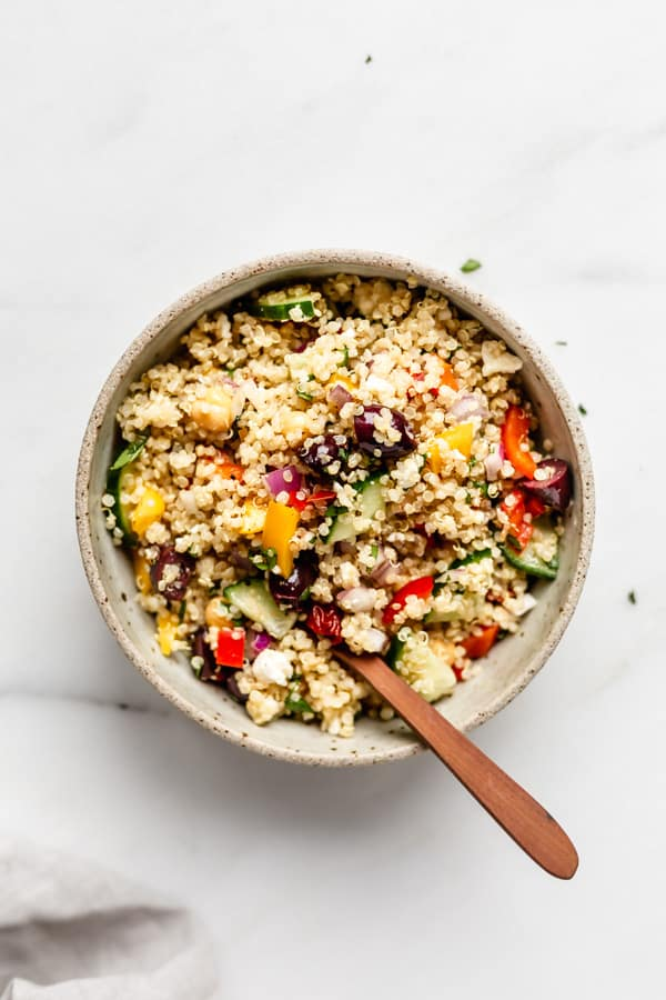 a bowl of mediterranean quinoa salad with a wood spoon