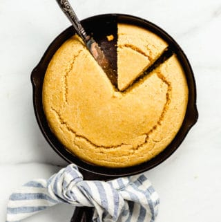 a cast iron skillet of vegan cornbread with a knife cutting into it