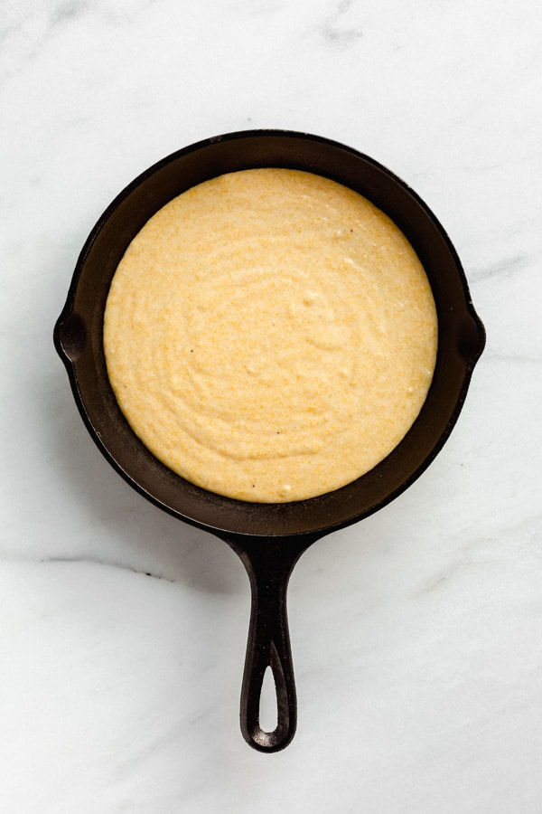 vegan cornbread batter in a cast iron skillet