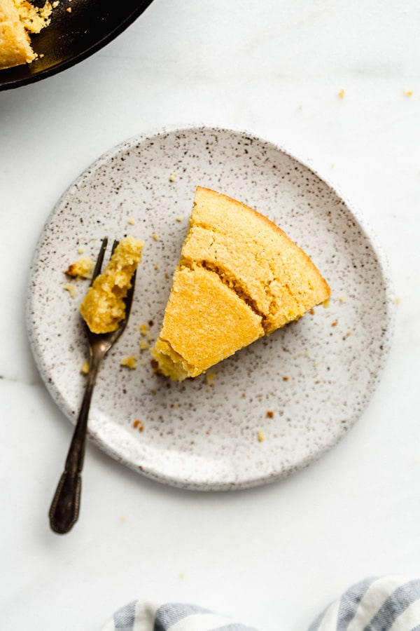 a slice of vegan cornbread on a speckled white plate