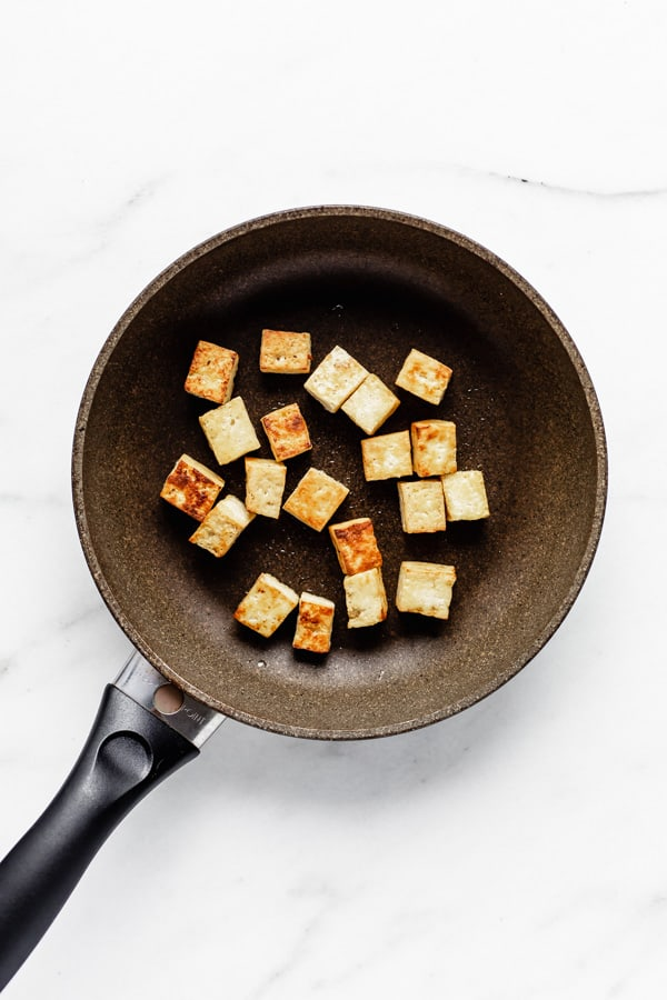 tofu cut into cubes in a frying pan