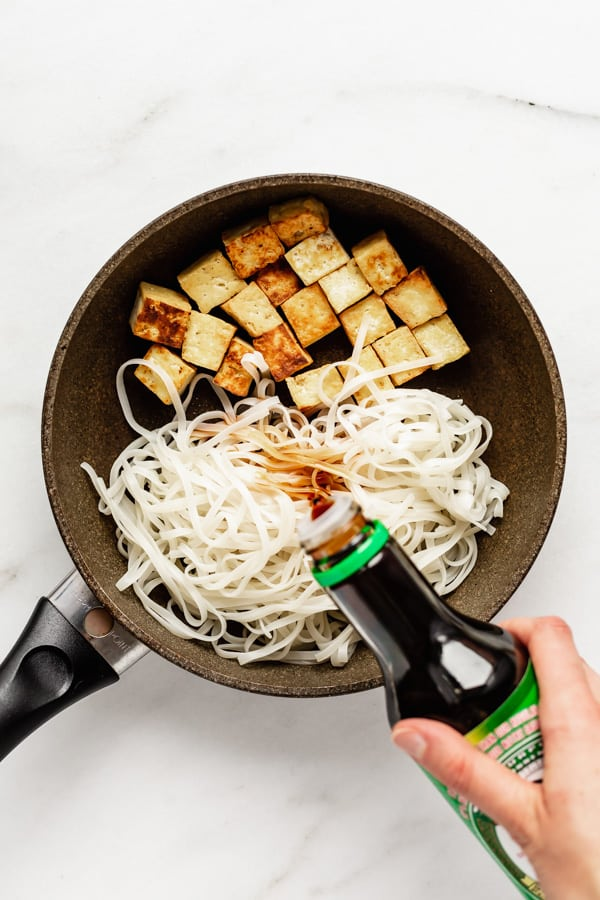 tou and rice noodles in a frying pan with a hand pouring soy sauce into the pan