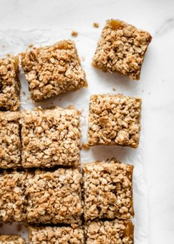 apple pie bars cut into squares on a piece of parchment paper