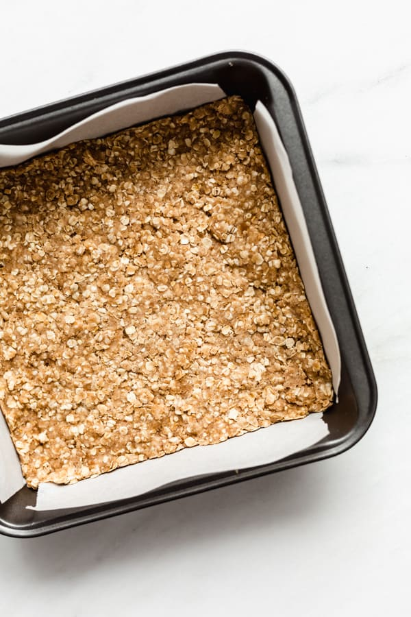 an 8x8 inch pan with apple pie bars crumble mixture pressed down in it
