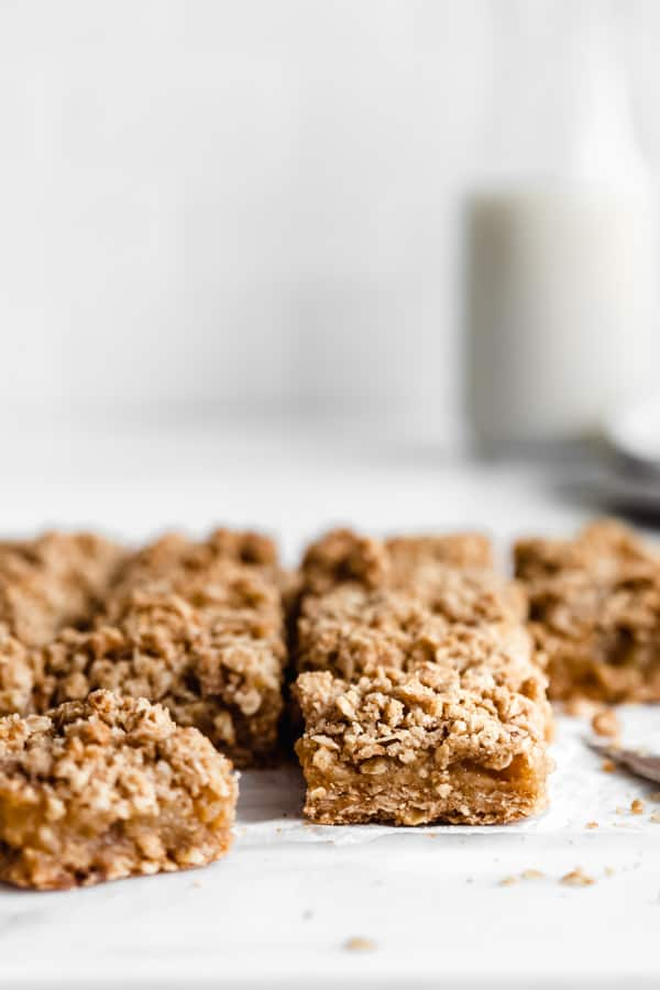 Apple pie bars cut up into squares on a white marble countertop
