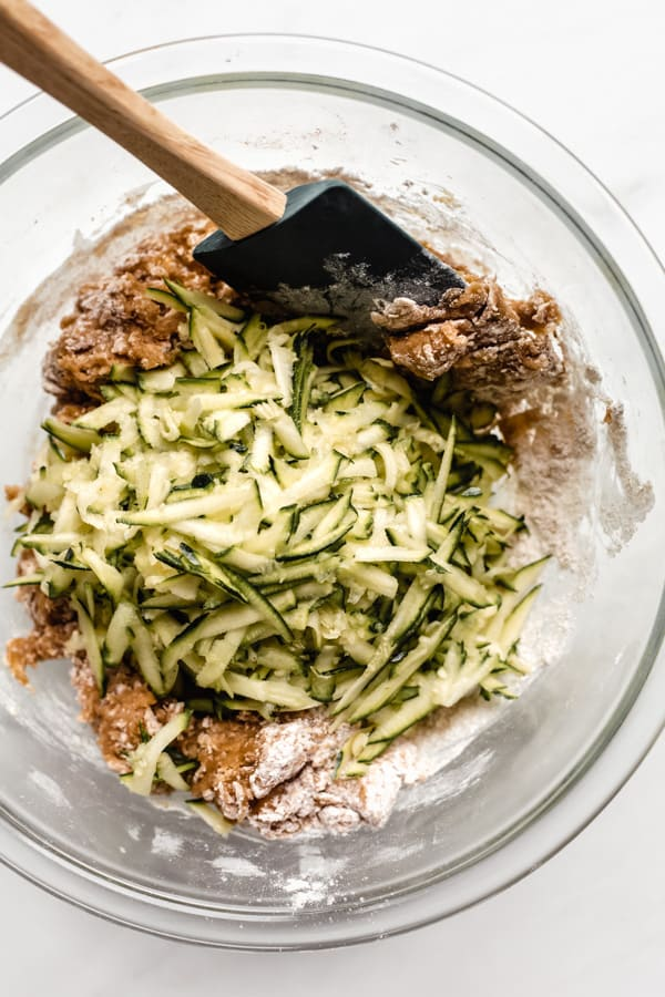 zucchini bread batter with a pile of grated zucchini on top in a clear mixing bowl