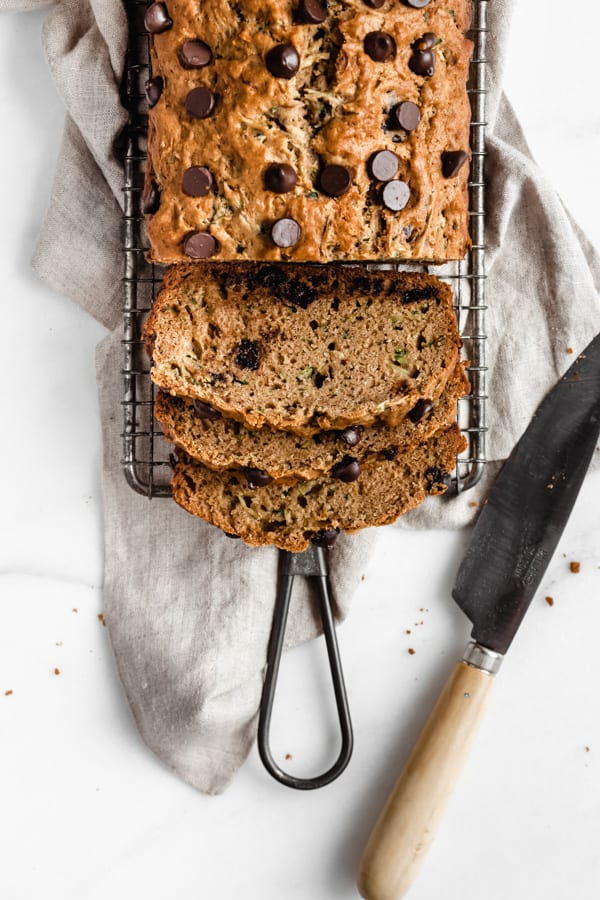 sliced chocolate chip zucchini bread on a cooling rack with a knife on the side