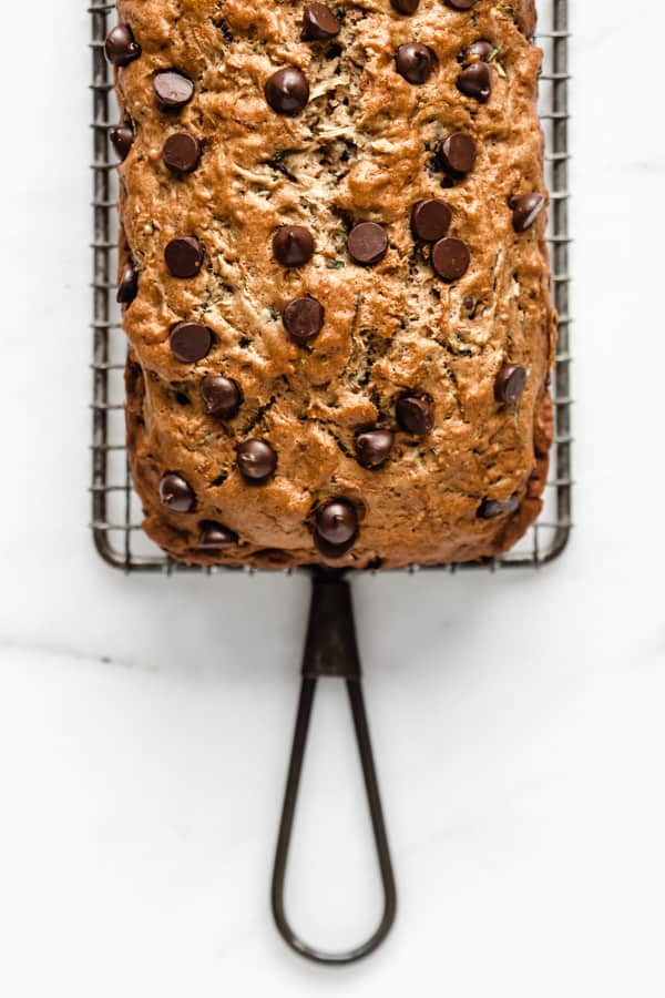 a chocolate chip zucchini bread topped with chocolate chips on a cooling rack