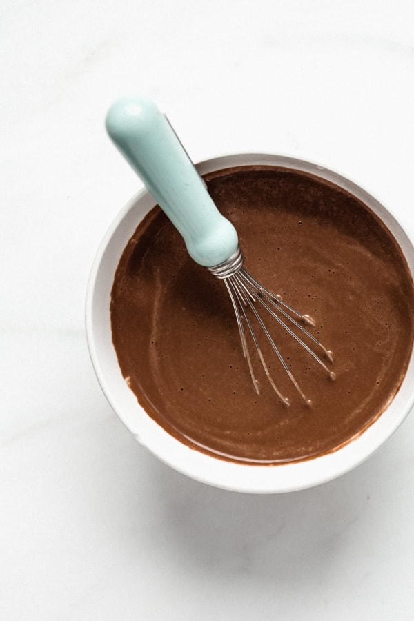 Chocolate cashew milk in a bowl with a small whisk