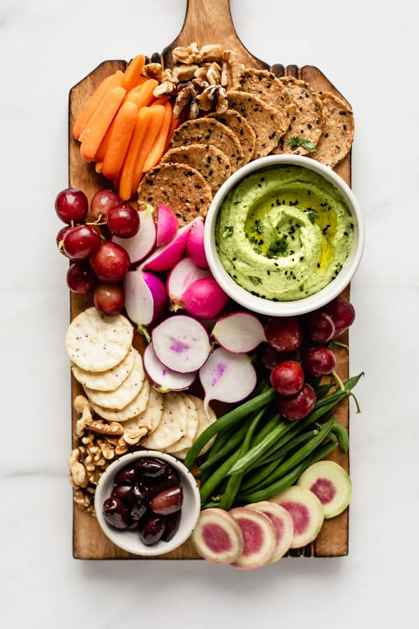 a wooden platter with veggies, fruits, crackers and edamame hummus on it