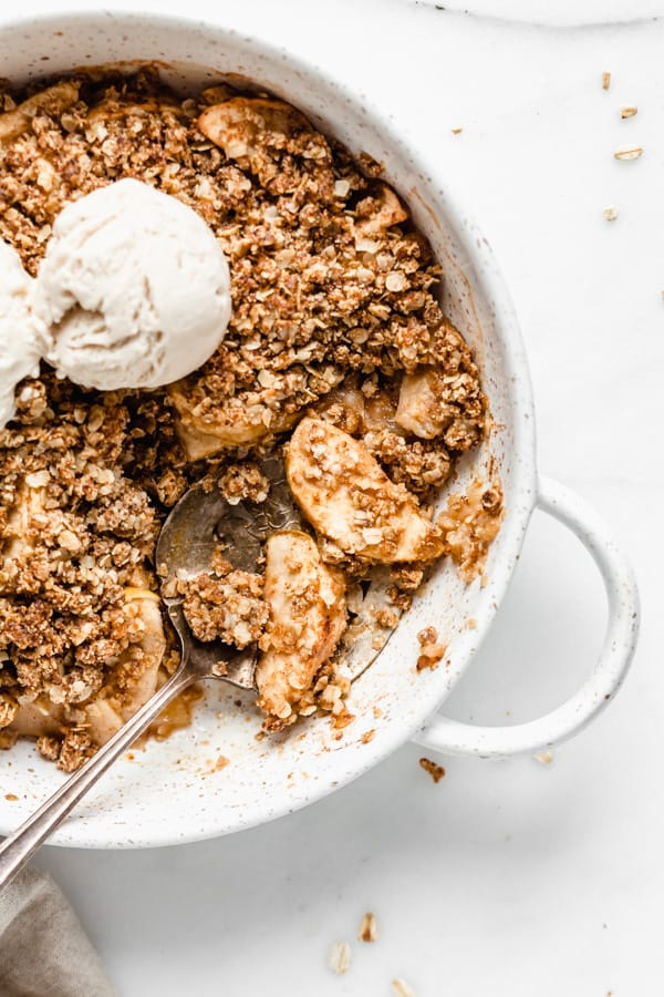 a serving spoon scooping some apple crisp out of a baking dish