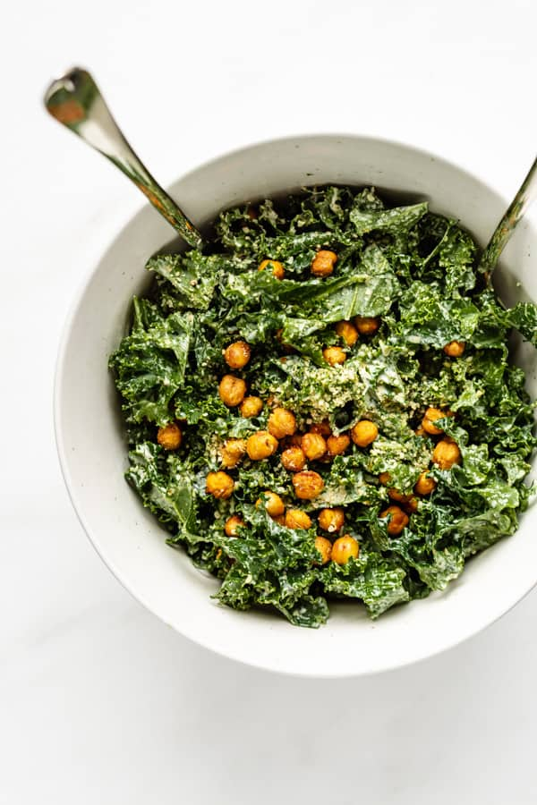 a top down view of kale caesar salad with crispy chickpeas and crumbled hemp seeds on top