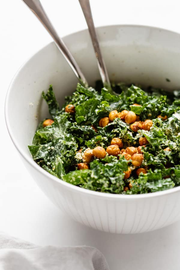 a serving bowl of kale Caesar salad topped with crispy chickpeas