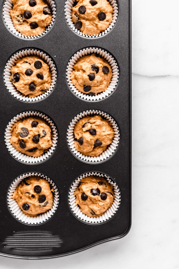 unbaked pumpkin chocolate chip muffins in a muffin pan