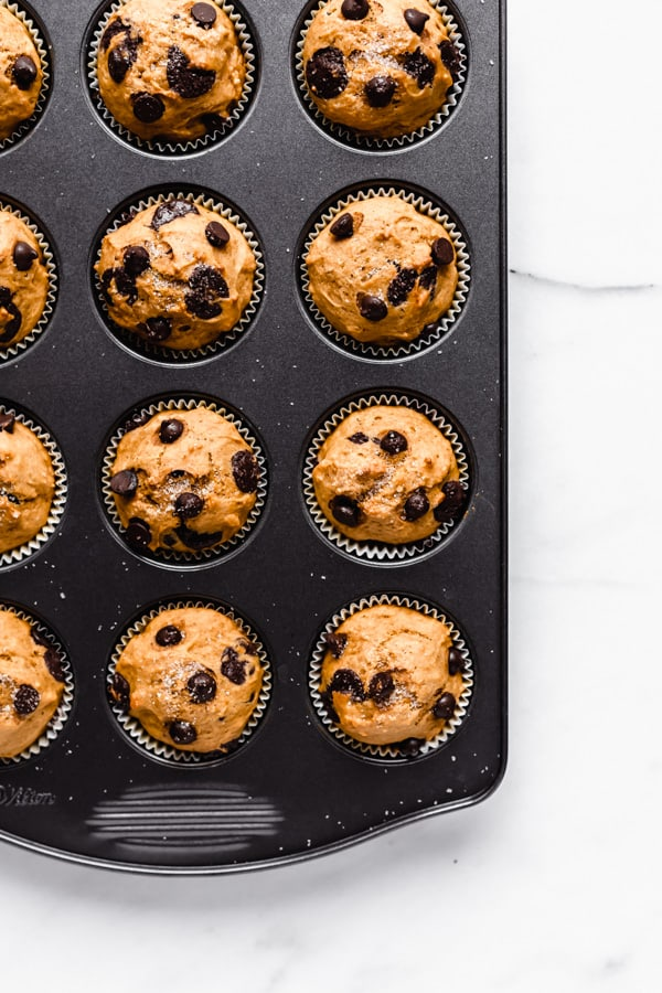 baked pumpkin chocolate chip muffins in a baking pan