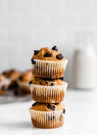 three pumpkin chocolate chip muffins stacked on top of each other