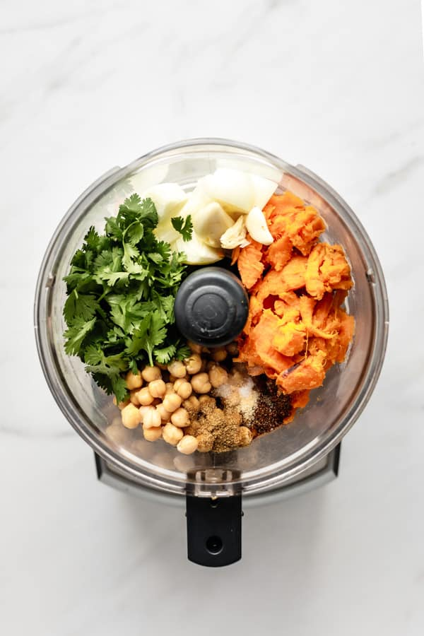 a food processor filled with ingredients for sweet potato falafel