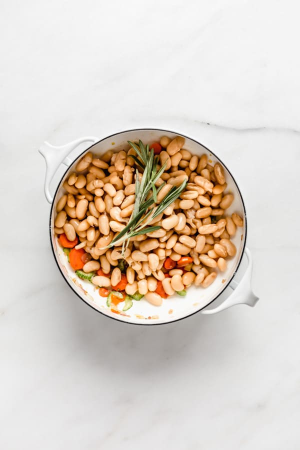 A white pot with white beans and a sprig of rosemary in it