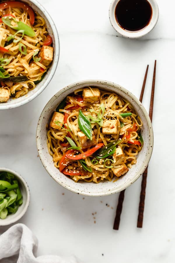 Singapore noodles in a speckeld ceramic bowl with wooden chopsticks on the sie