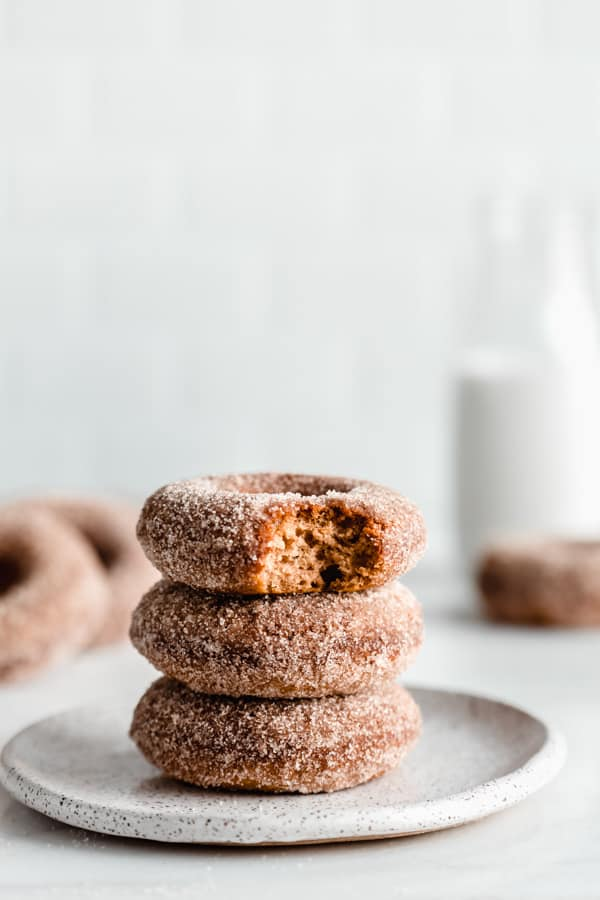 A stack of three apple cider donuts on a white speckled plate