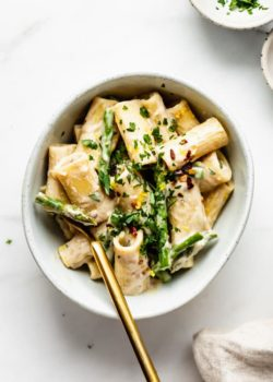 a bowl of lemon asparagus rigatoni noodles topped with small bowls of parsley and chilli flakes on the side