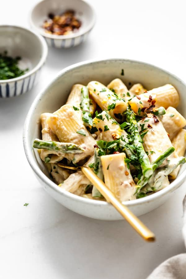 creamy rigatoni pasta in a white bowl with a gold fork
