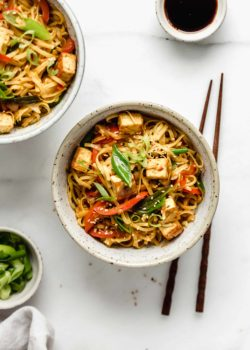 a ceramic bowl filled with Singapore noodles and chopsticks on the side