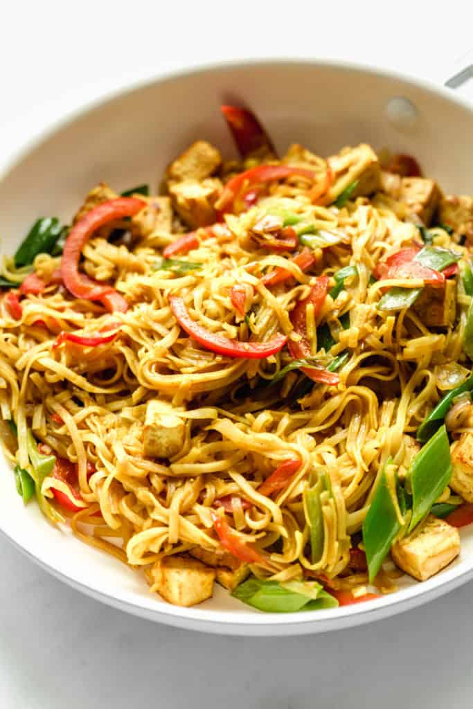 singapore noodles in a pan with peppers and tofu