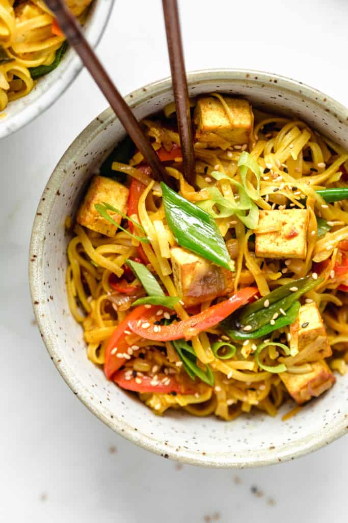 a bowl of singapore noodles with sliced green onions and sesame seeds on top
