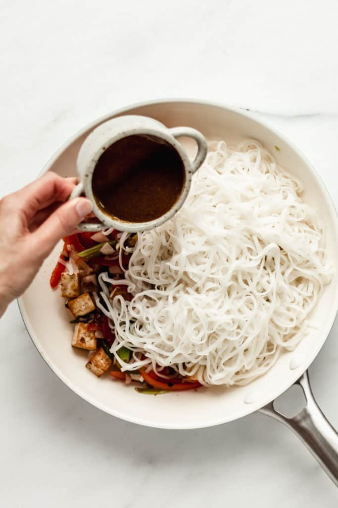 rice noodles in a pan with a hand pouring sauce onto them