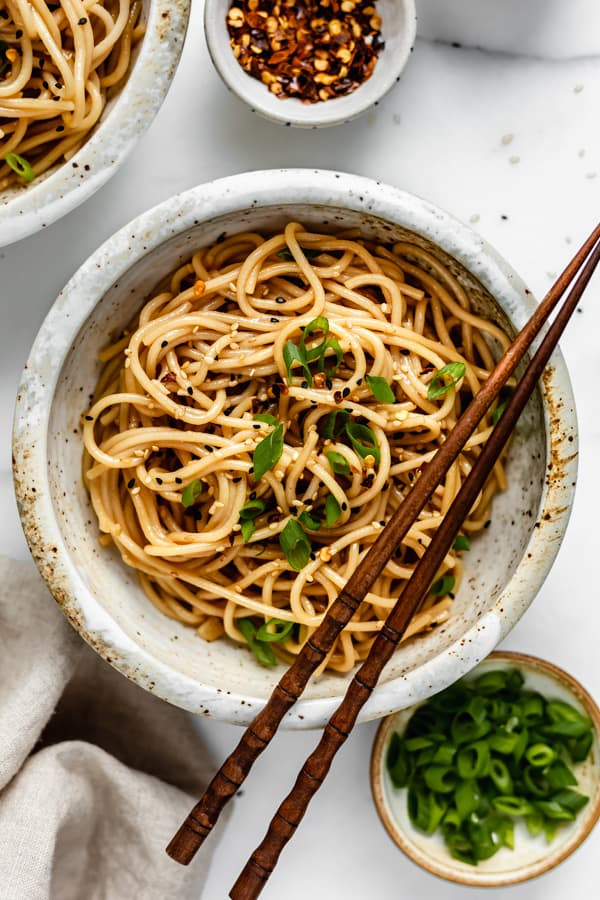 A bowl of noodles topped with green onions and wooden chopsticks on top of the bowl