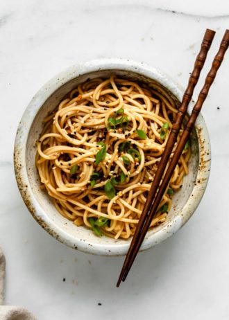 A top down view of a bowl with asian spaghetti in it topped with green onions