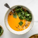A bowl of butternut squash soup topped with cilantro