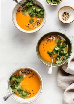 Three bowls of butternut squash soup on a marble countertop