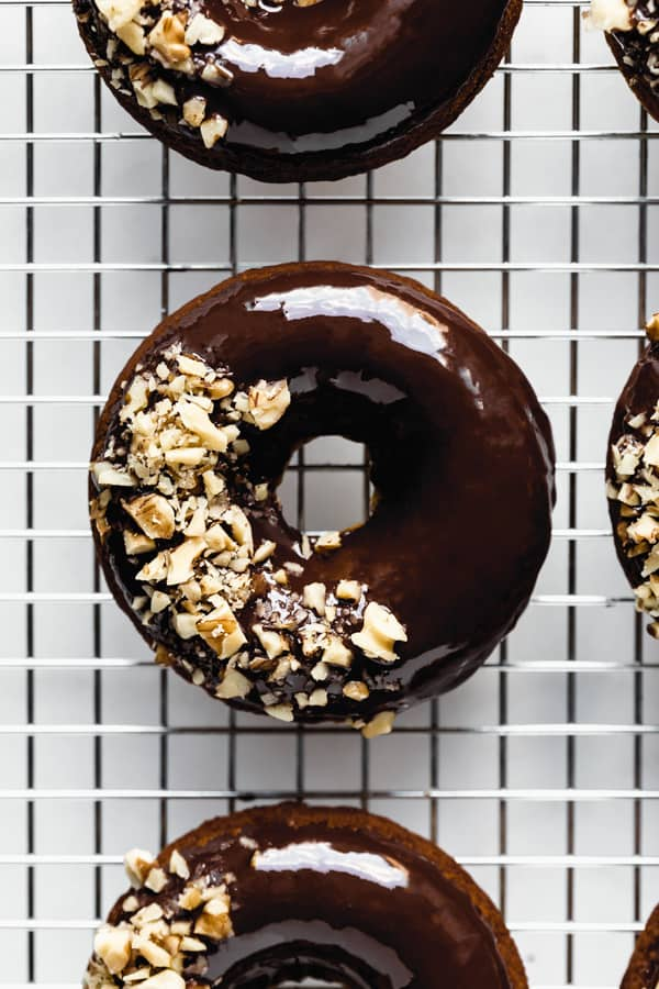 a close up of a donut topped with chocolate glaze and crushed walnuts on a silver cooling rack