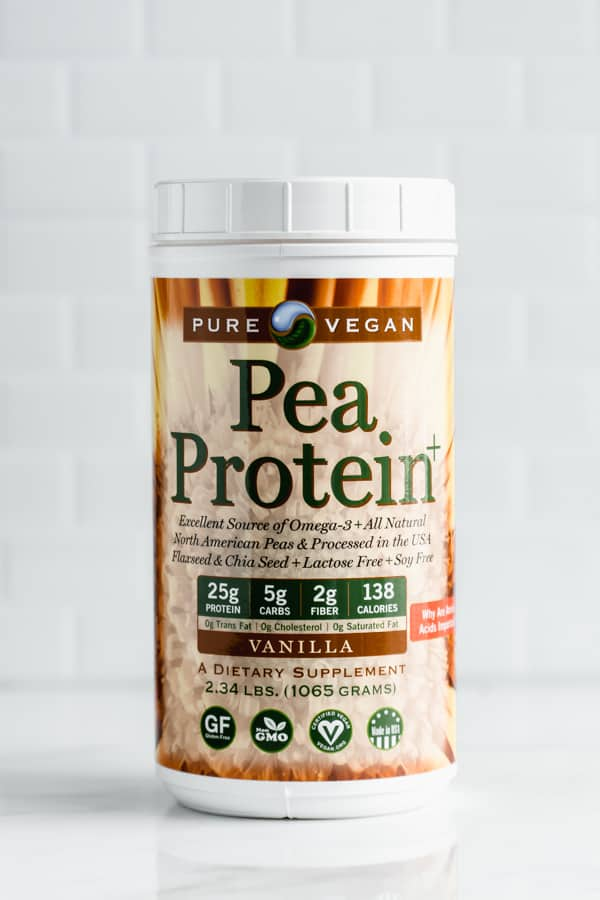 a container of vanilla pea protein on a marble counter