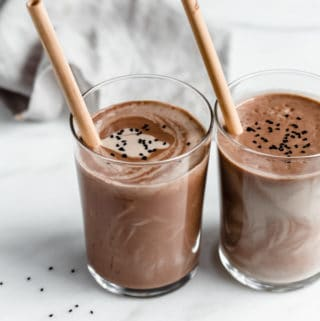 two glasses of chocolate tahini smoothies on a marble counter