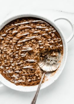 cinnamon roll baked oatmeal in a round baking dish with a serving spoon in it