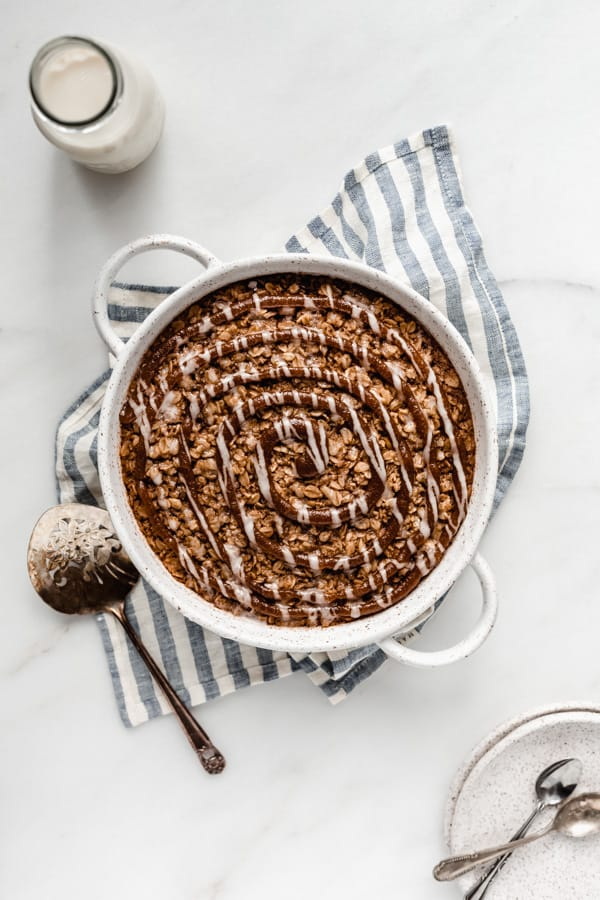 baked oatmeal in a round baking dish on a striped blue napkin topped with cinnamon sugar swirl