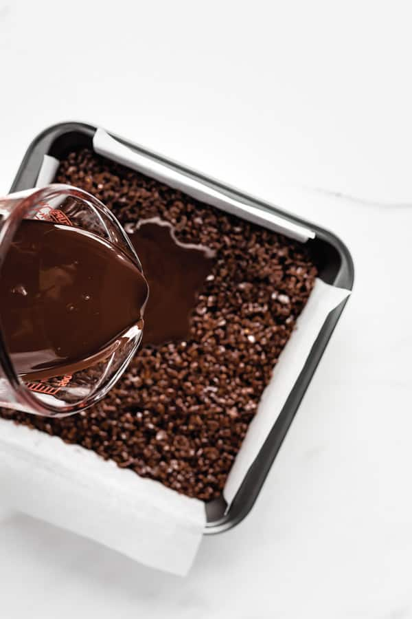 a measuring cup pouring chocolate into a pan of chocolate rice Krispie treats
