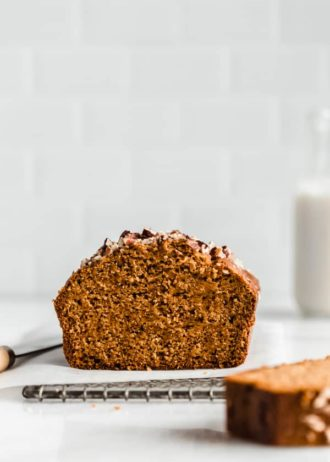 pumpkin bread with a slice missing on a cooling rack
