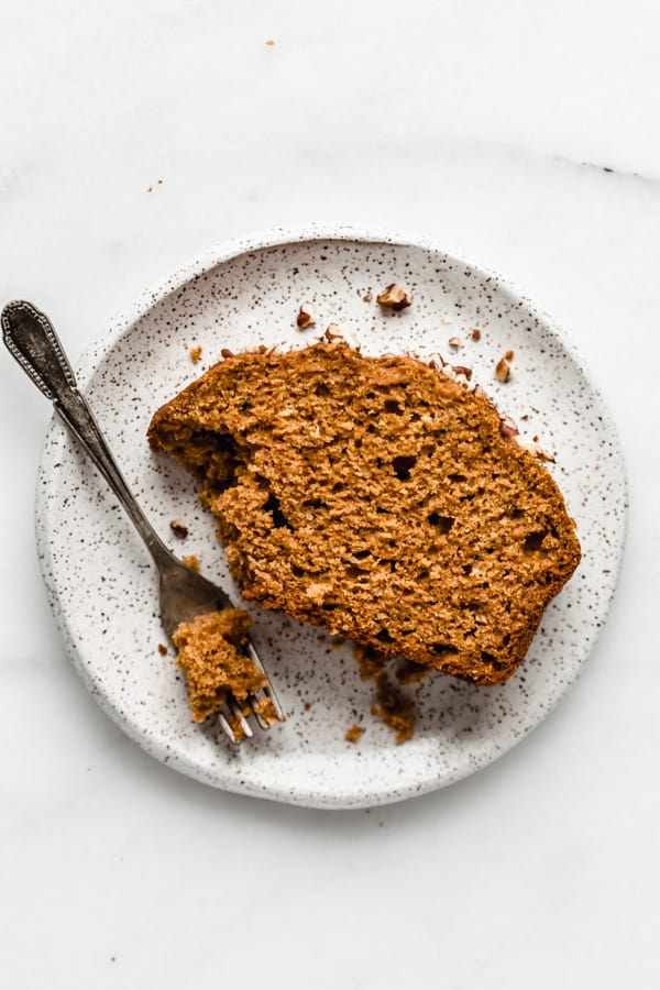 A slice of pumpkin bread on a white speckled plate