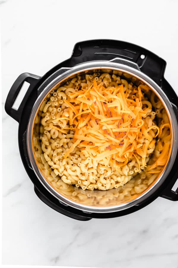 macaroni in an instant pot with a pile of orange shredded cheese on it