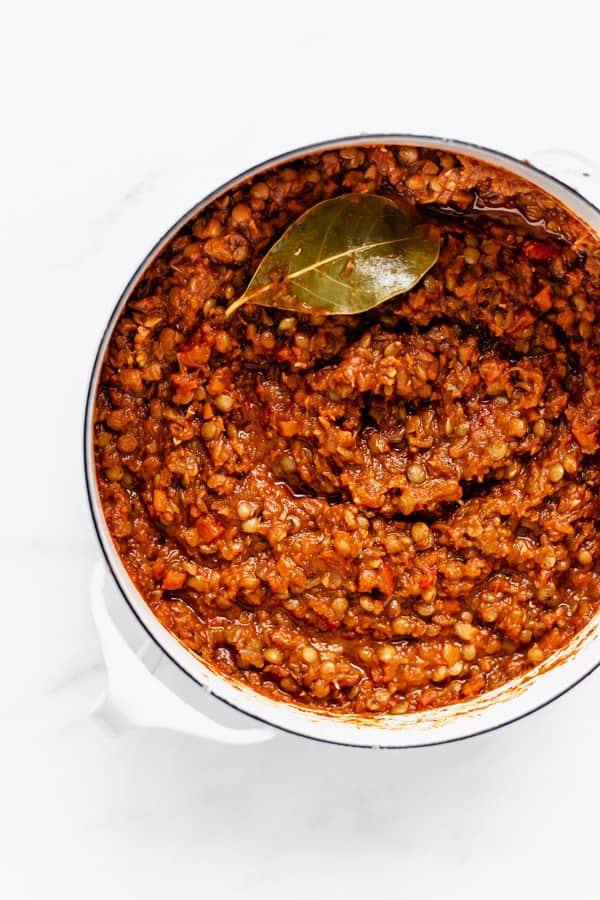 a pot filled with lentil bolognese and a bay leaf on top