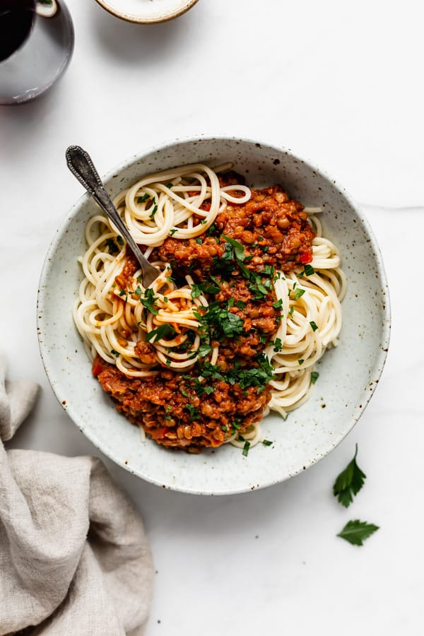 spaghetti with lentil bolognese in a white speckeld pasta bowl and a napkin on the side