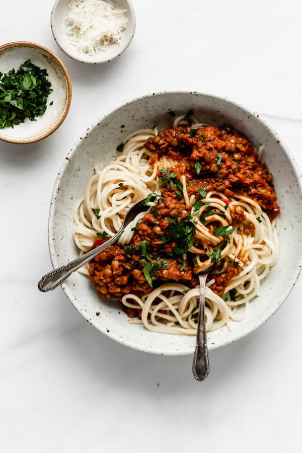 a white bowl filled with spaghetti and lentil bolognese and two smaller bowls on the side with parsley and parmesan cheese