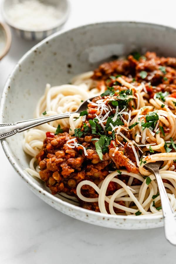 a close up of spaghetti in a bowl topped with lentil bolognese