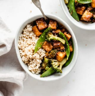 a bowl of rice and tofu stir fry with a fork in it