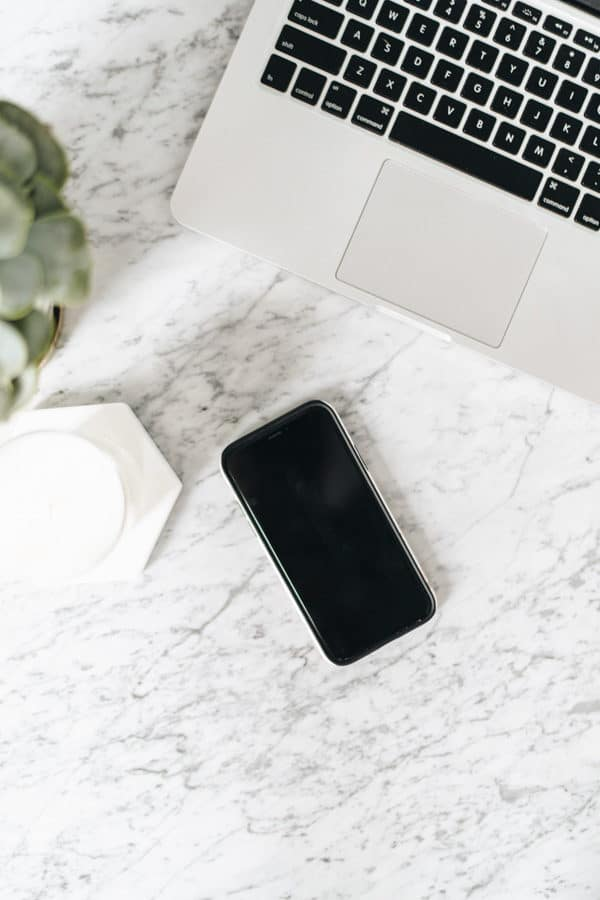 an iphone and laptop on a marble table