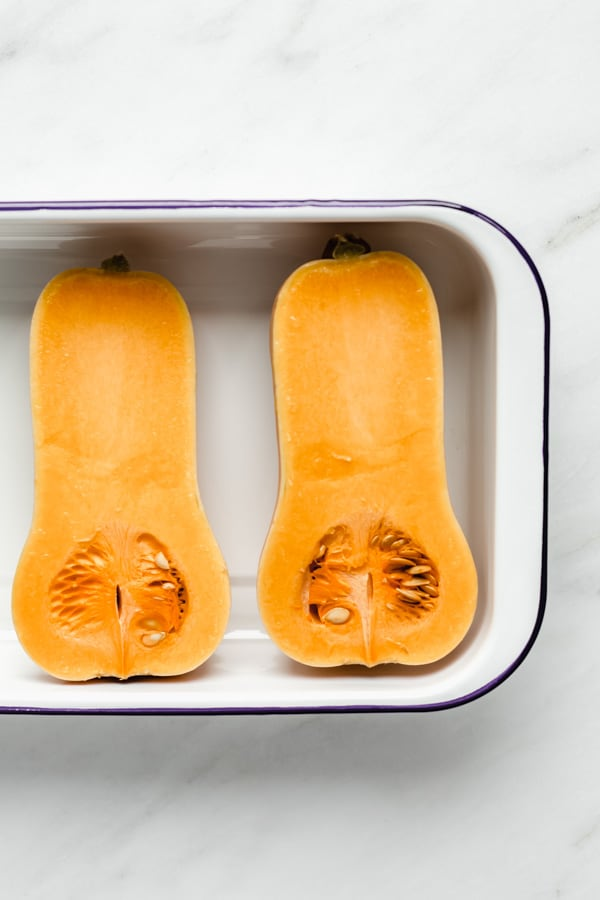 two halves of butternut squash in a white roasting pan